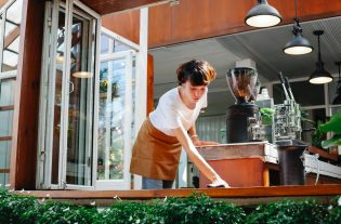 woman wiping wooden board of cafe